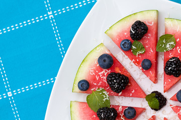Watermelon pizza slices with fresh blueberry, blackberry, chips of white chocolate and green mint leaves.