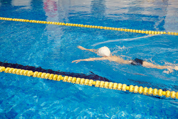 High angle of unrecognizable school age boy swimming fast face down underwater on pool lane separated by yellow lines