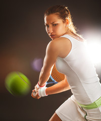 Tennis female player hitting ball with backhand.Studio shot.