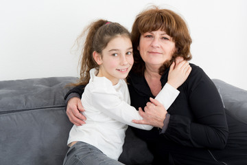a grandmother and her granddaughter make a hug on the sofa in the house family