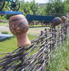 clay jug on wooden fence