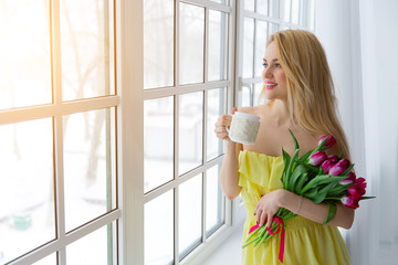 Portrait of beautiful woman with tulip bouquet and cup tea. sunlight.
