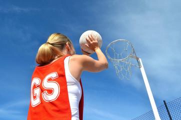 Woman shoots a netball into a netball ring