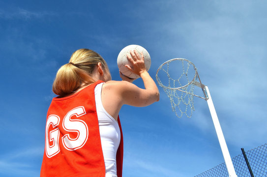 Woman shoots a netball into a netball ring