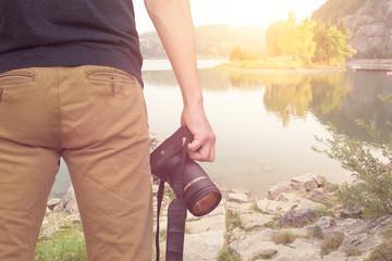 photographer with camera mountain lake