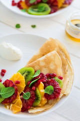 Thin crepes with fresh kiwi, orange, sicilian orange, honey, cream and mint leaves on white rustic wooden table. Selective focus
