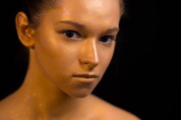 Professional model posing with bronze art makeup on her face