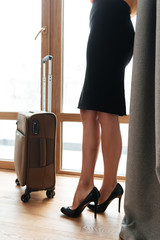 Woman in high heels standing at the window with suitcase
