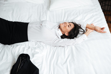 Smiling young business woman laying and stretching in bed