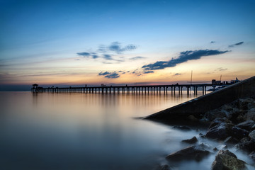 Dark rock dam in blue ocean on twilight sunset and wooden bridge extended into the sea with water reflection., long exposure photography., the concept of lonely, sadness, depressed and broken heart.