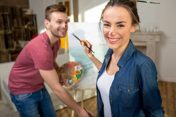 Happy young couple of artists with paint on noses having fun while painting together