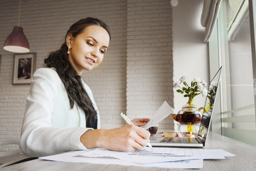 Confident woman sitting at table and taking notes on paper