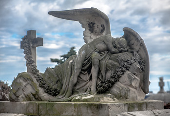 Sculpture of a sad angel on a cemetery