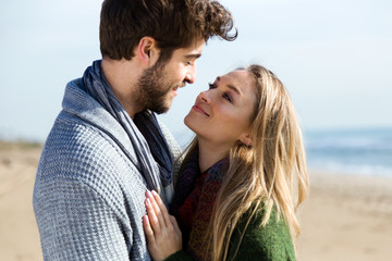 Beautiful young couple in love in a cold winter on the beach.