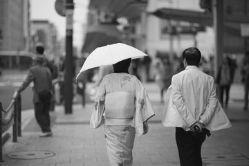 A woman with an umbrella in kimono walking down the street next to a man.