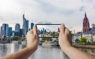 Hand with smartphone taken pictures of Frankfurt am Main skyline