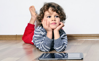 Beautiful kid playing games on a tablet. Boy sitting on the floor and looking on the display of a tablet watching cartoons.