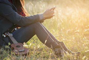 Closeup of a beautiful woman using a cell phone. She  wearing jeans and boots. She is sitting in the meadow and ukulele lay beside her.