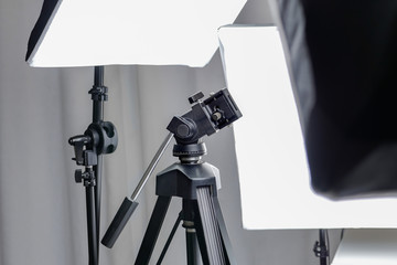 Camera tripod in a photo studio with lightning equipment