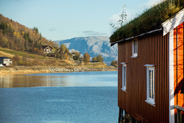 Red wooden house on stilts with a grass roof. Mountains in the background