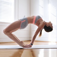 Side view of woman exercising yoga in the gym