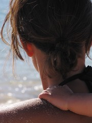Cropped Image Of Child Keeping On Mother Shoulder At Beach