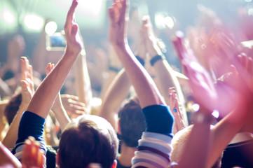 hands fans at a concert