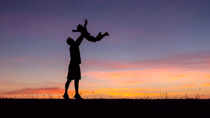 Silhouette of a happy family of father and child  run on meadow in the summer on the nature.