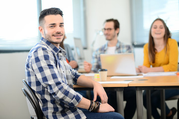 portrait of a young man in casual wear working in creative business startup company office with coworker people in background