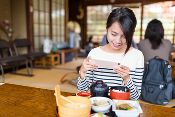 Woman taking photo with cellphone on her meal