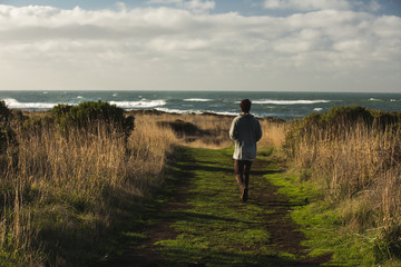 Man walking on grass towards sea view