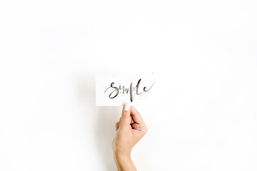 Minimal pale composition with girl's hand holding card with word Simple written in calligraphic style on paper on white background. Flat lay, top view