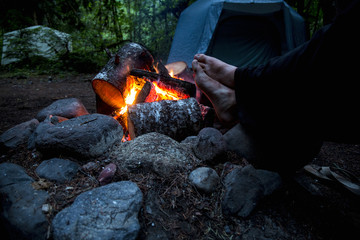 Low section of man warming feet near campfire in the forest