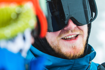 Two men wearing snow sport headgear, communicating face to face