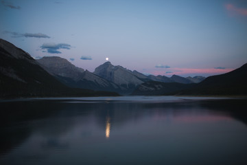 Reflection of moon on lake by mountains