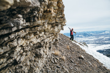 Skier walking by rock formations, holding skis