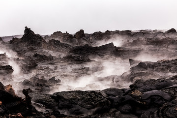 Steaming lava pieces under light rain