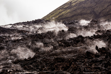Barren lava fields steaming in light rain with green volcano slope in background