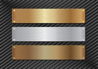 three metal plaques on black background