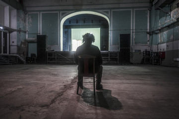 lonely man sitting in an abandoned movie theater and watching a scene