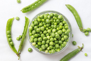 Raw Peas in Glass Bowl, Isolated on White Background, Top View