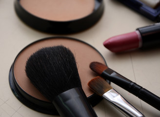 A bronzer powder, make up brushes and lipstick placed on a white table in make up studio. Close up view.