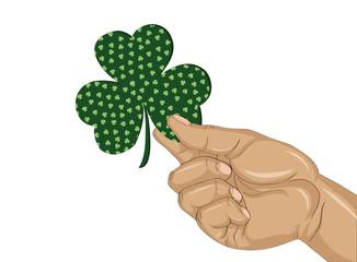 Hand holds ornate clover tree-leaf. Celebration concept St. Patrick's Day.