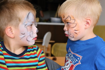 Two boys with painted faces talking to each other