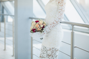 Beautiful bride in white wedding dress holding bouquet