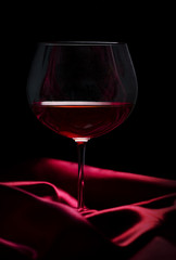 Glass of wine on red silk