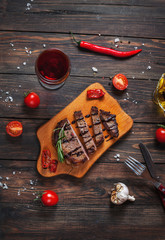 Grilled beef steak seasoned with spices served on a wooden board with fresh cherry tomato and red hot chili peppers