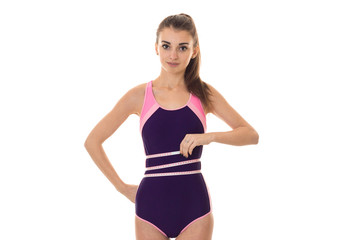 a young girl in a sports suit stands directly looks into the camera and takes the waist Ribbon
