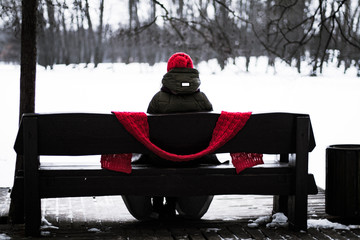 Portrait of a beautiful young girl in a red cap with a scarf, which is sitting back on a bench in the park in winter and looks into the distance