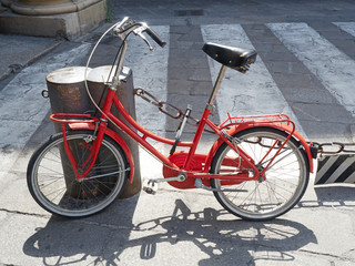 Red old fashioned bicycle parked street